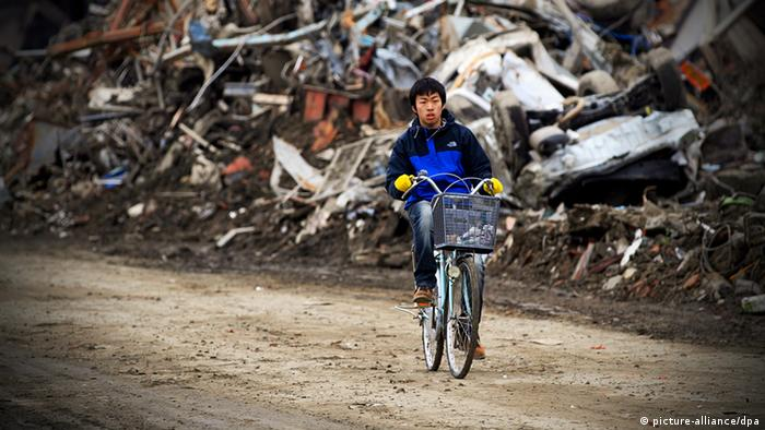 A young boy rides his bike trough the rubble in Ishinomaki, Miyagi Prefecture (Photo: EPA/STEPHEN MORRISON)