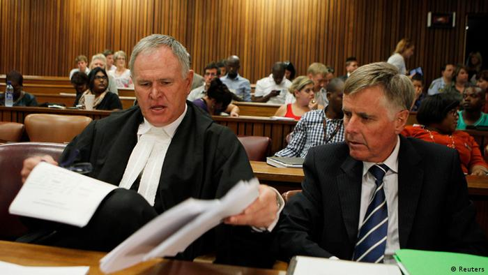Oscar Pistorius's lawyers Barry Roux (L) and Brian Webber prepare documents before the start of the application to appeal some of his bail conditions at a Pretoria court in Pretoria March 28, 2013. The lawyers of South African paralympic sprinter Pistorius are set to appeal some of his bail conditions after the sports star was charged with the pre-meditated murder of his girlfriend Reeva Steenkamp. REUTERS/Siphiwe Sibeko (SOUTH AFRICA - Tags: CRIME LAW SPORT)