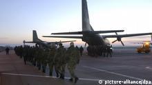 [659182] Erste Bundeswehrstaffel nach Afghanistan gestartet Die ersten 70 Bundeswehrsoldaten für die internationale Schutztruppe in Afghanistan (ISAS) marschieren am 8.1.2002 auf dem Militärflughafen Köln-Wahn zu ihren Transall-Flugzeugen. Die zwei Maschinen fliegen zunächst nach Eindhoven, wo 30 niederländische Soldaten zu der Einheit stoßen. Über die Türkei sollen die Männer dann nach Afghanistan fliegen und den Flughafen Bagram bei Kabul am 9.1. erreichen. Insgesamt können laut Bundestagsbeschluss bis zu 1200 deutsche Soldaten nach Afghanistan entsandt werden. Die Aufgabe der in Köln gestarteten Vorausstaffel ist es, die Ankunft der weiteren deutschen Soldaten vorzubereiten.