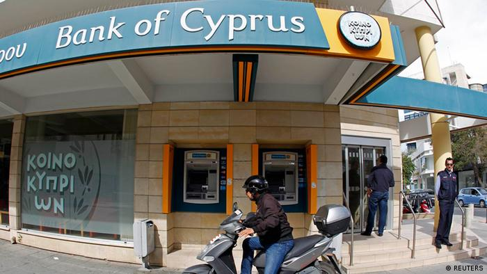 A man prepares to ride his motorbike after leaving a branch of Bank of Cyprus shortly after it opened in Nicosia March 28, 2013. (Photo: Reuters/Bogdan Cristel)