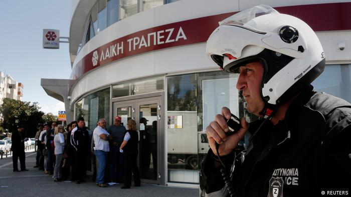 A police officer speaks on a radio as customers queue up outside a branch of Laiki Bank, Cyprus. (Photo: REUTERS/Yorgos Karahalis)