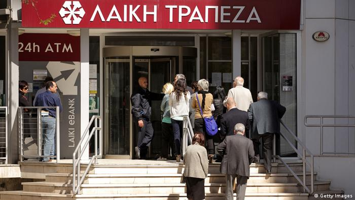 A security guard stands at the entrance of a branch of the Cyprus Popular Bank PATRICK BAZ/AFP/Getty Images