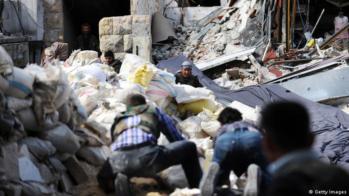Syrian opposition fighters crossing rubble while coming under fire by Syrian army snipers in Aleppo