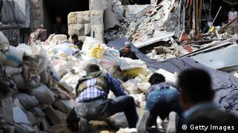 Syrian opposition fighters try to cross the rubble as they come under fire by Syrian army snipers during clashes in the northern city of Aleppo (c) BULENT KILIC/AFP/Getty Images