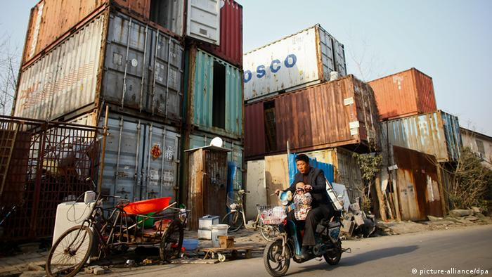 A cycler taking a child drives past homes converted from shipping containers in the suburb of Shanghai, China, 8 March 2013. People stand outside shipping containers serving as their accommodation, as a car passes through a street, in Shanghai. The containers, which house different families, were set up by the landlord, who charges a rent of 500 yuan ($ 80) per month for each container.
