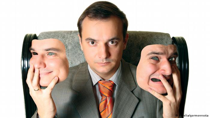 Человек держит в руках две маски: на одной он изображен улыбающимся, на другой - разъяренным.