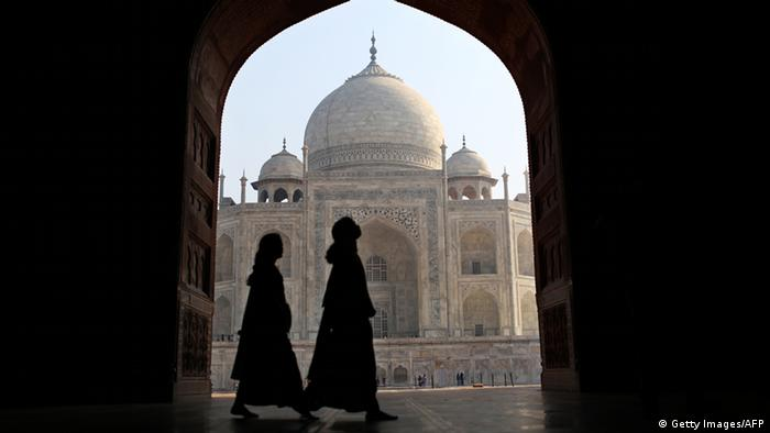 Indian tourists walk past an archway at the historic Taj Mahal in Agra on November 28, 2012. A highway, that opened up in August 2012, connecting India's Taj Mahal tourism town of Agra with the capital New Delhi has slashed driving time by more than half. The 165-kilometre (100-mile) Yamuna Expressway promises a two-hour drive through the crowded towns of Uttar Pradesh state to Agra, where the Taj Mahal draws almost three million domestic and foreign tourists a year. AFP PHOTO/ Andrew Caballero-Reynolds (Photo credit should read Andrew Caballero-Reynolds/AFP/Getty Images)