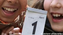 ARCHIV - ILLUSTRATION - Zwei Kinder lachen in Kaufbeuren (Schwaben) hinter einem Kalenderblatt, welches das Datum 1. April zeigt, aufgenommen am 27.03.2008. Am 1. April veralbern sich Menschen gegenseitig mit Streichen. Die Redewendung «in den April schicken» ist in Deutschland seit 1618 bekannt. Unklar ist, woher der Aprilscherz stammt. Foto: Karl-Josef Hildenbrand dpa +++(c) dpa - Bildfunk+++