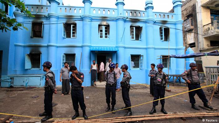Police stand in front of a mosque and school dormitory that were damaged by a fire in Yangon April 2, 2013. An electrical fire at an Islamic school in Myanmar's biggest city killed 13 children early on Tuesday, authorities said. The children, all boys, died of suffocation in the fire at the dormitory of a school next to the mosque in Yangon at about 2:40 a.m., neighbours and officials said. REUTERS/Soe Zeya Tun (MYANMAR - Tags: DISASTER EDUCATION RELIGION TPX IMAGES OF THE DAY)