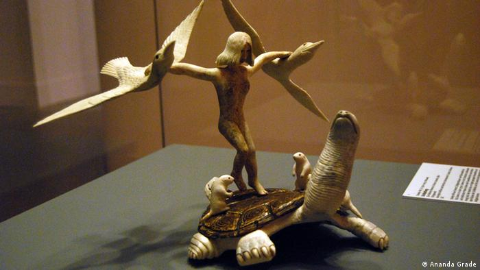 A small sculpture of a woman held by birds and standing on a turtle.