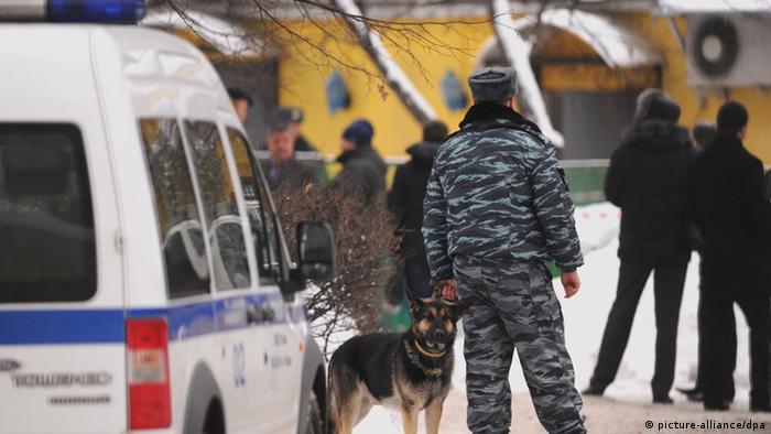Полицейский с собакой стоит рядом с машиной полиции