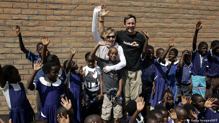 US Pop Star Madonna (C) flanked by her Malawian adopted Children, David (in front of her) and Mercy (to her right) and BuildOn CEO Jim Ziolkowskiare (to her left), are pictured on April 2, 2013 oustide of a classroom with school children at Mkoko Primary School in the region of Kasungu, central Malawi, one of the schools her Raising Malawi organization has built jointly with US organization BuildOn. Madonna, said to be the single largest international philanthropic donor to Malawi, also supports childcare in the country which is home to nearly a million children orphaned by AIDS. She arrived in Malawi on March 31 with the two children she adopted from the small landlocked African country. AFP PHOTO / AMOS GUMULIRA (Photo credit should read AMOS GUMULIRA/AFP/Getty Images)