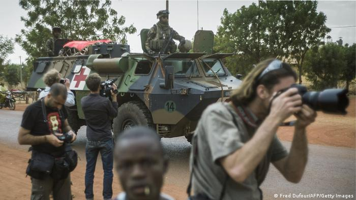 Photoreporters work as French army troopers arrive at the base camp, on January 25, 2013 in Sevare. French and Malian troops advanced on the key Islamist stronghold of Gao after recapturing the northern town of Hombori as the extremists bombed a strategic bridge to thwart a new front planned in the east. The French-led assault against the radical Islamists controlling northern Mali entered its third week with a strong push into the vast semi-arid zone amid rising humanitarian concerns for people in the area facing a dire food crisis. AFP PHOTO / FRED DUFOUR (Photo credit should read FRED DUFOUR/AFP/Getty Images)