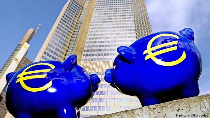 Two bright blue euro-piggy-banks in front of the European Central Bank building