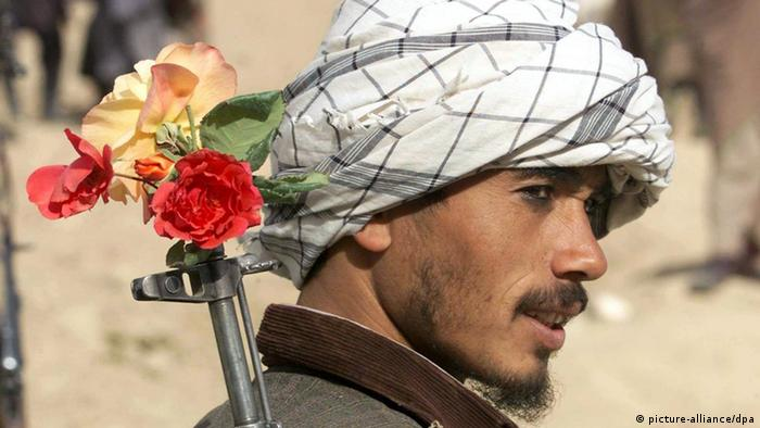 An Afghan with flowers in the barrel of his Kalashnikov rifle slung over his shoulder,