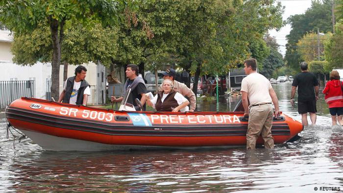 Argentine firemen evacuate a woman from her flooded home after heavy rains flooded a large part of the city, in La Plata April 3, 2013. REUTERS/Enrique Marcarian