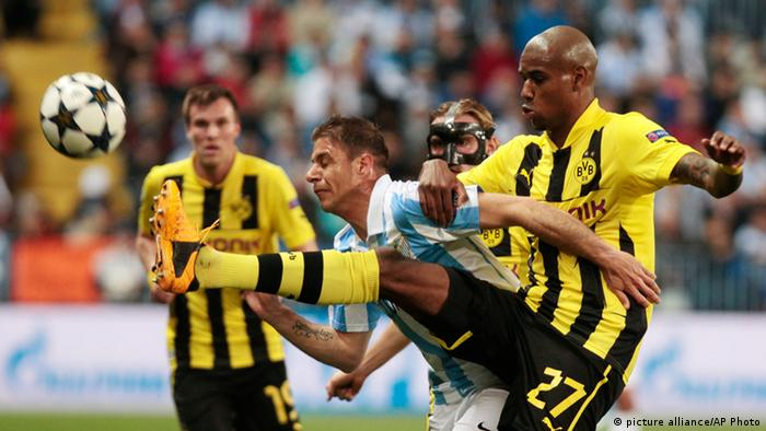 [38565333] Spain Soccer Champions League Malaga's Jeremy Toulalan, center, is challenged by Dortmund's Felipe Santana of Brazil, right, during the Champions League quarterfinal first leg soccer match between Malaga CF and Borussia Dortmund in Malaga, Spain, Wednesday, April 3, 2013. (AP Photo/Miguel Angel Morenatti)