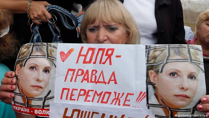 A supporter of the former Ukrainian Prime Minister Yulia Tymoshenko holds her portraits with slogan 'Yulia - truth will triumph!', during their protest in front of the Kiev Pecherskyi District Court, Ukraine, 17 August 2011