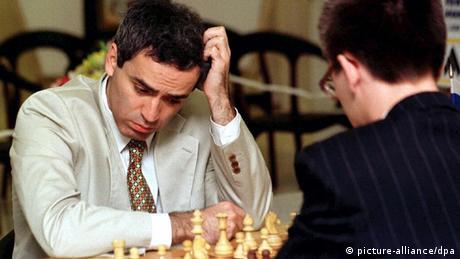 Schachspieler Garri Kasparow sitzt vor einem Schachbrett und kratzt sich am Kopf (picture-alliance/dpa)