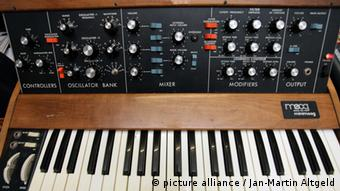 Ein Minimoog, ein analoger, monophoner Synthesizer. Der Minimoog war der erste Synthesizer in kompakter Bauart. Unter Liebhabern gilt das Instrument als der Heilige Gral der Synthesizer. Benannt ist er nach Firmengruender Robert Moog. Beruehmt ist der Minimoog vor allem fuer seinen warmen Klang: das charakteristische, durchsetzungsfaehige Filter sorgt gleichwohl für knarzende Baesse wie auch für schrille Lead-Sounds. Zahlreiche Bands und Musiker verwendeten und verwenden den Miminoog - darunter Kraftwerk, Bob Marley, Jean Michel Jarre, Air etc. A Minimoog, a monophonic synthesizer. The Minimoog was the fist Synthesizer with a tight design. The Instrument is helt as the Holy Grail for Synthesizer-Fans. The Originator was Robert Moog, who is also founder of the Company Moog Music Inc. The Minimoog is famous for it's warm sound, caused by a characteristical Filter. Many bands an musicians used the Minimoog and use it still, amongst others Kraftwerk, Bob Marley, Jean Michel Jarre and Air.
