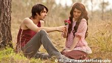 Be My Valentines TeresaYehPhotography - Fotolia 38650540 2012; stock; romantic; love; gift; shy; valentines day; flirting; young adult; boyfriend; girlfriend; couple; spring; caucasian; outdoors; flower; pink