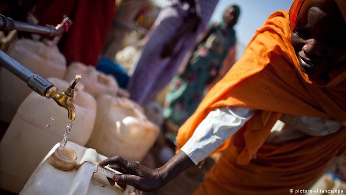 Eine Frau in Darfur füllt Wasserbehälter auf
