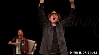 Ein Mann gestikuliert wild und schreit. Hinter ihm spielt eine Frau Ziehharmonika. (c)MEYER_ORIGINALS