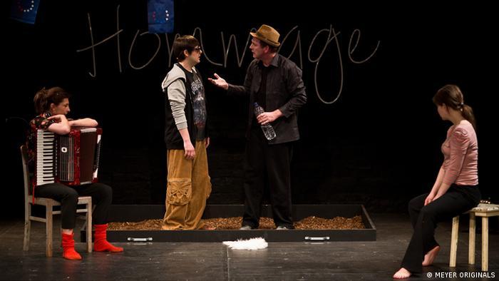 Auf einer Theaterbühne stehen sich zwei Männer gegenüber. Links sitzt eine Frau mit einer Ziehharmonika. Rechts eine junge Frau, die mit dem Gesicht abgewandt ist. (c)MEYER_ORIGINALS