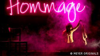 Eine junge Frau sitzt oben ohne, mit dem Rücken zu uns gewandt. Im Hintergrund hängt eine Leuchttafel mit der Aufschrift Hommag (c)MEYER_ORIGINALS
