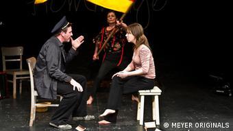 Ein Mann redet mit einer Frau. Hinter ihnen schwenkt eine Frau die deutsche Fahne. (c)MEYER_ORIGINALS