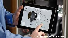 Am Fraunhofer Institut für graphische Datenverarbeitung IGD in Darmstadt hält ein Mitarbeiter einen mobilen Computer, der eine Explosionszeichnung von Bauteilen darstellt. (Foto: Fraunhofer IGD)