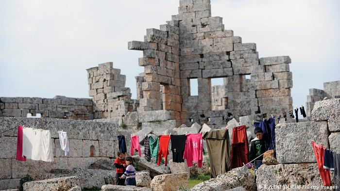 Syrian refugees hang out their clothes to dry in the ruins of the ancient Roman city of of Serjilla