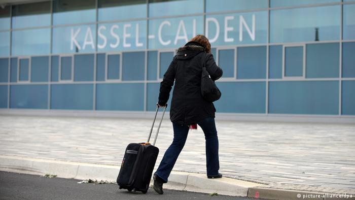 Eine Frau mit Koffer geht auf den Terminal des Flughafens Kassel-Calden zu (Foto: dpa)