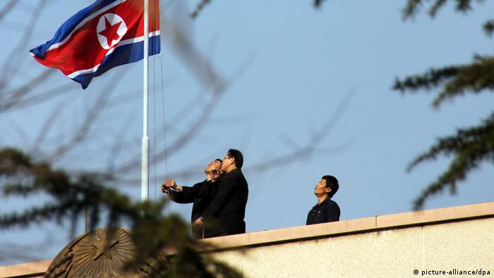 Officials at the North Korean Embassy in Beijing, China, lower the national flag in the morning of 19 December 2011 to mourn the death of North Korean leader Kim Jong-il (EPA/YONHAP SOUTH KOREA OUT +++(c) dpa - Bildfunk+++ )