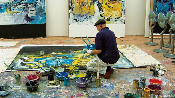 Georg Baselitz kniet in seinem Atelier, umringt von Farbeimern, vor einem Gemälde auf der Erde