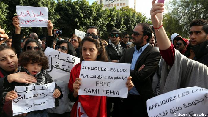 epa03518158 Tunisian protesters hold banners and shout slogans during a demonstration outside of Tunisian National Constituent Assembly to demand the liberation of Sami Fehri, TV producer and director of Ettounsiya Television, in Tunis, Tunisia, 26 December 2012. Fehri is facing corruption charges for his association with Belhassen Trabelsi, the brother-in-law of former president Zine el-Abidine Ben Ali, and the misappropriation of national television resources for Cactus Productions company, which Fehri co-owned with Trabelsi. EPA/MOHAMED MESSARA