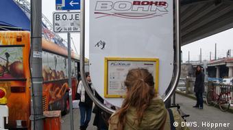 Eine junge Frau steht vor einem Aukunftsschild am Kölner Busbahnhof. (Foto: DW/Stephanie Höppner)