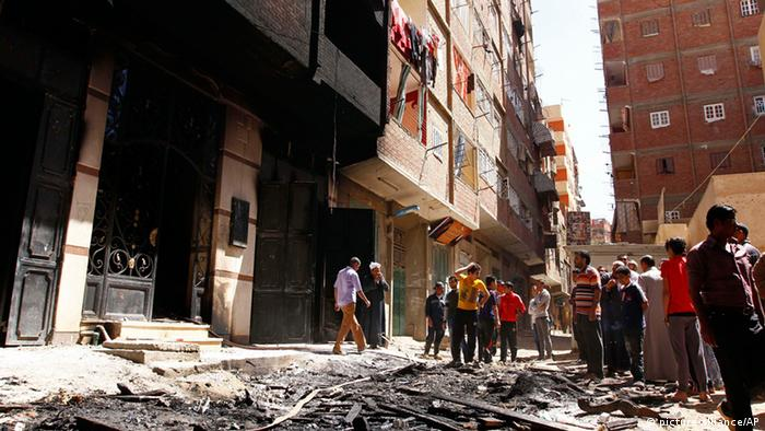 Onlookers gather at the house of Egyptian Christian, Samir Iskandar which was burned during clashes between Muslims and Christians (Photo: AP Photo/Mohammed Nouhan, El Shorouk Newspaper)