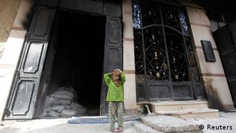 A girl stands in front of a burnt house belonging to a Muslim REUTERS/Amr Abdallah Dalsh