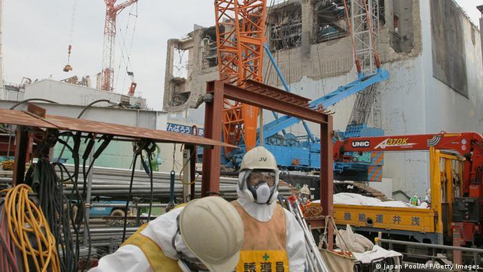 Menschen in Schutzanzügen auf dem Gelände des Atomreaktors in Fukushima