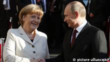German Chancellor Angela Merkel welcomes Russian President Vladimir Putin for the opening of the Hannover Fair at the Congress Center in Hannover, Germany, Sunday April 7,2013. (AP Photo/Frank Augstein)