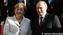 German Chancellor Angela Merkel welcomes Russian President Vladimir Putin for the opening of the industrial Hannover Fair at the Congress Center in Hannover, Germany, Sunday April 7,2013. (AP Photo/Frank Augstein)