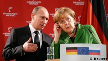 Russian President Vladimir Putin translates a question from a journalist for German Chancellor Angela Merkel during a news conference following their tour through the Hanover Messe on the first day of the industrial trade fair, in Hanover April 8, 2013. Russia is the partner country of the Hanover fair 2013, which runs from April 8 -12. REUTERS/Fabrizio Bensch (GERMANY - Tags: POLITICS BUSINESS)