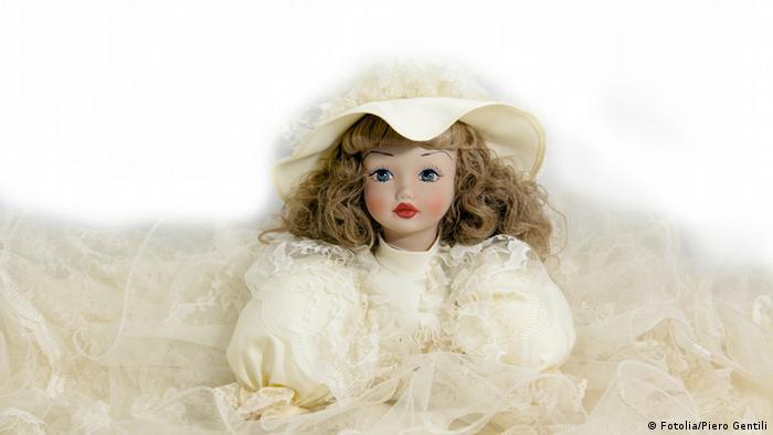 Eine Puppe in einem weißen Hochzeitskleid mit einem schön verzierten Hut