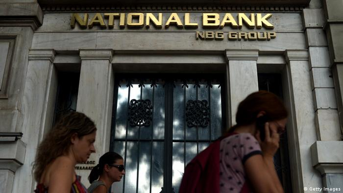People pass a branch of National Bank of Greece in Athens ARIS MESSINIS/AFP/GettyImages