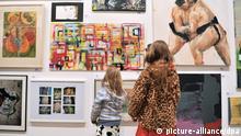 Zwei Kinder sehen sich Bilder in einem Museum an