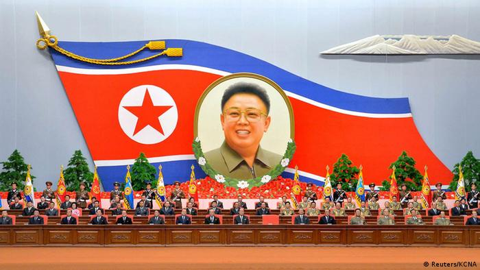 North Korean officials assemble under a huge flag with Kim Jong Il's photo. (Photo: REUTERS/KCNA)