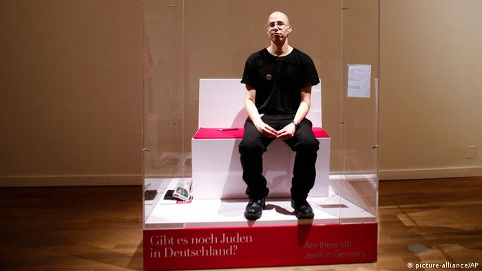 In this March 22, 2013 file photo, Israeli Ido Porat prepares to be the first person acting as the 'Jew in a glass box', on the first day of the exhibition The Whole Truth, everything you always wanted to know about Jews at the Jewish Museum in Berlin. (AP Photo/Markus Schreiber, File)