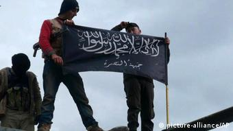 FILE - In this Friday, Jan. 11, 2013 file citizen journalism image provided by Edlib News Network, ENN, which has been authenticated based on its contents and other AP reporting, shows rebels from al-Qaida affiliated Jabhat al-Nusra waving their brigade flag as they step on the top of a Syrian air force helicopter, at Taftanaz air base that was captured by the rebels, in Idlib province, northern Syria. The Arabic words on the flag reads: There is no God only God and Mohamad his prophet, Jabhat al-Nusra. Last month, militants inside Iraq killed 48 Syrian government troops who had sought refuge from the war in their country _ an ambush that regional officials now say is evidence of a growing cross-border alliance between two powerful Sunni jihadi groups _ Al-Qaida in Iraq and the Nusra Front in Syria. The U.S. designates both as terrorist organizations, and the purported alliance is further complicating the equation for the West as it weighs how much to support the rebel movement.(AP Photo/Edlib News Network ENN, File)