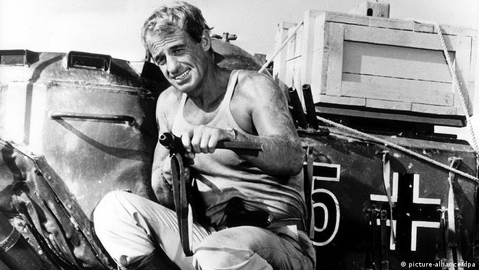 Jean-Paul Belmondo as Sgt. Augagneur in The Vultures (1984) (Jean-Paul Belmondo) putzt eine Waffe(picture-alliance/dpa)